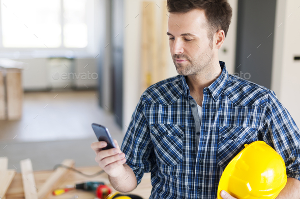 Construction worker with contemporary mobile phone - Stock Photo - Images