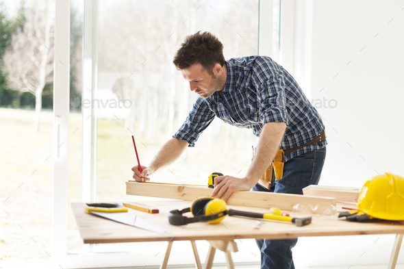 Focus man measuring wooden planks - Stock Photo - Images