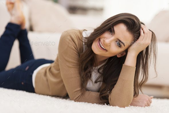 Attractive woman lying on carpet at home - Stock Photo - Images