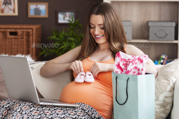 Future mother doing online shopping at home - Stock Photo - Images
