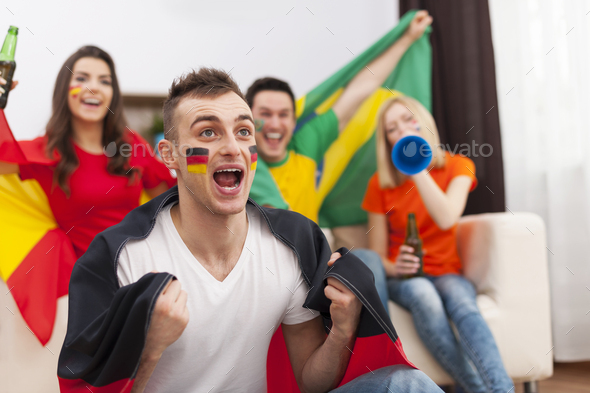Excited german man with her friends cheering football match - Stock Photo - Images