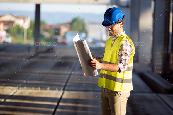 Picture of construction site engineer looking at plan - Stock Photo - Images