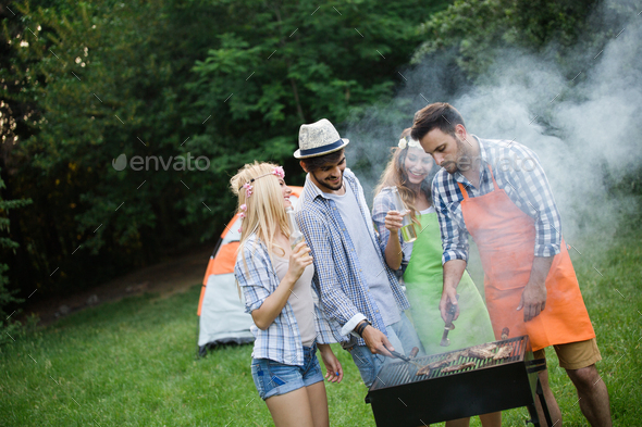 Group of friends making barbecue in the nature - Stock Photo - Images
