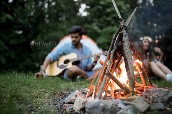 Friends playing music and enjoying bonfire in nature - Stock Photo - Images