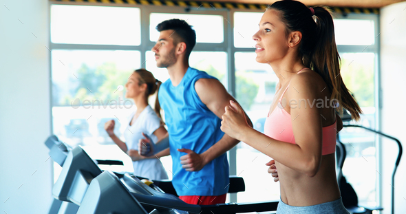 Group of friends exercising on treadmill machine - Stock Photo - Images