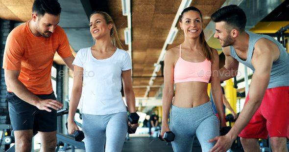 Two attractive women exercising with personal trainers - Stock Photo - Images