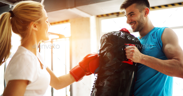 Beautiful woman exercising in gym with trainer - Stock Photo - Images