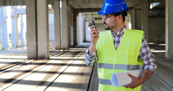 Male architect communicating on walkie-talkie at site - Stock Photo - Images