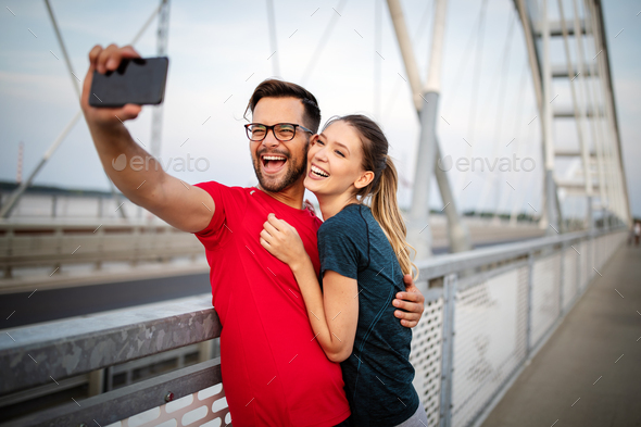 Sport man and woman making selfies. Happy couple hugging and posing for camera - Stock Photo - Images