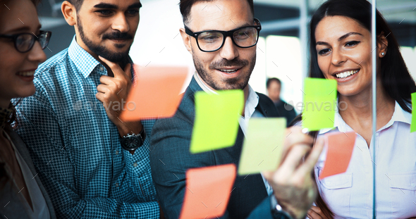 Businesswoman using sticky notes at office to plan project - Stock Photo - Images