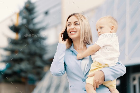 Portrait of a successful business woman in blue suit with baby - Stock Photo - Images