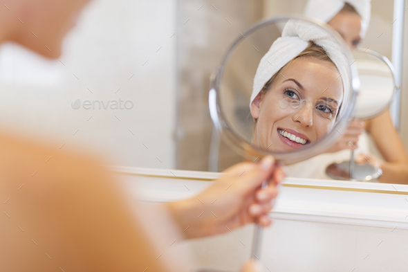 Beautiful woman looking herself reflection in small mirror - Stock Photo - Images