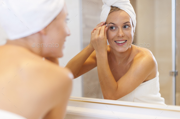 Woman tweezing eyebrows in front of mirror - Stock Photo - Images