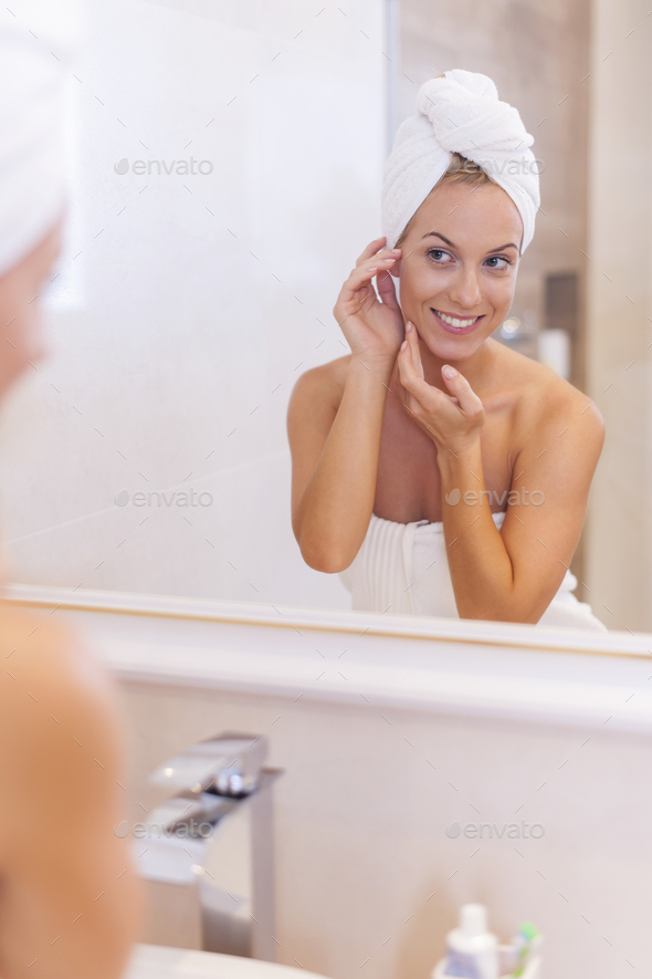 Woman looking herself reflection in mirror after the shower - Stock Photo - Images