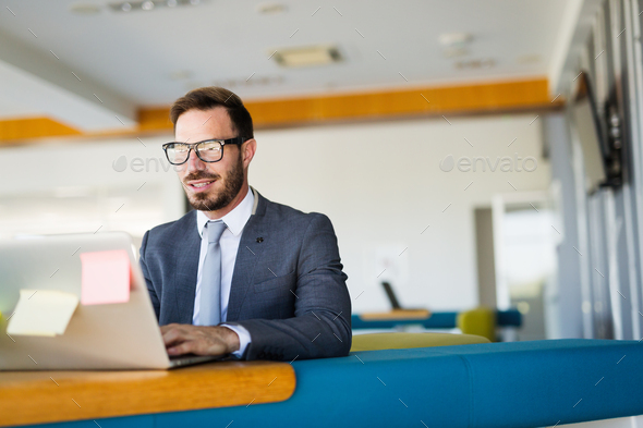 Handsome businessman working on laptop in office - Stock Photo - Images