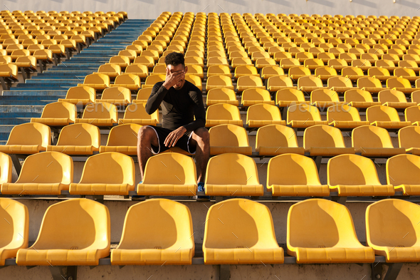 African American sportsman covering face with hand resting after run among empty stadium seats - Stock Photo - Images