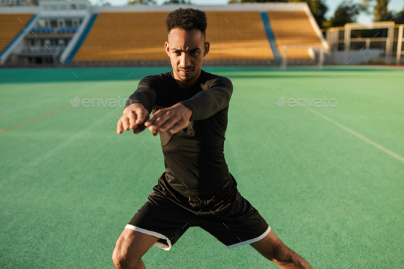 Young serious African American sportsman heavily doing exercises during workout at city stadium - Stock Photo - Images