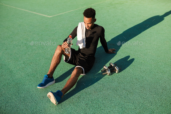 Young attractive African American sportsman resting after workout at stadium - Stock Photo - Images