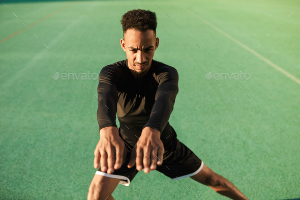 Young angry African American sportsman doing exercises during hard workout at stadium - Stock Photo - Images