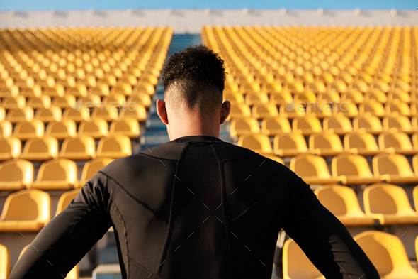 Back view of young strong African American sportsman among empty stadium seats - Stock Photo - Images