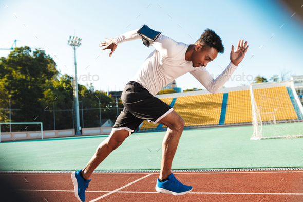 Side view of young African American sportsman running on racetrack during workout at city stadium - Stock Photo - Images