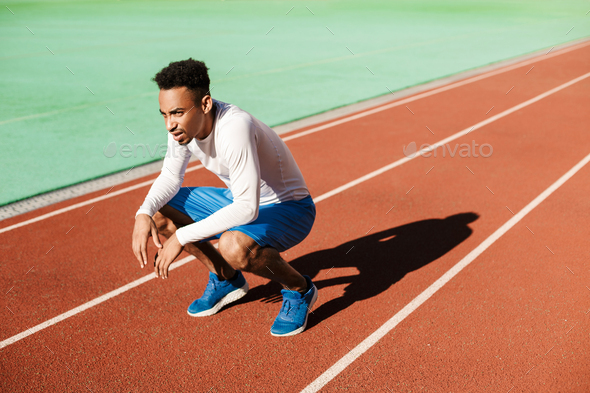 Young tired African American sportsman sit on one's haunches and resting after run at city stadium - Stock Photo - Images