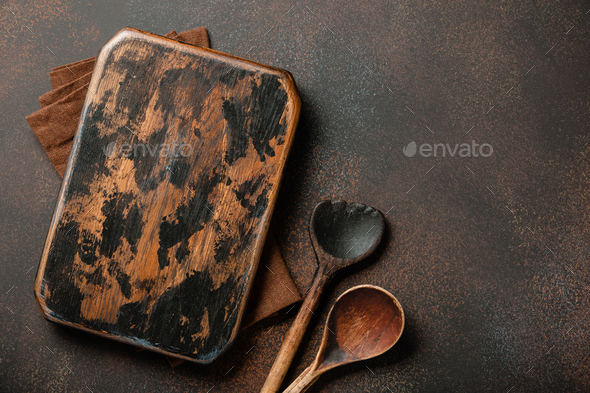 Cooking background with vintage cutting board and wooden spoons - Stock Photo - Images