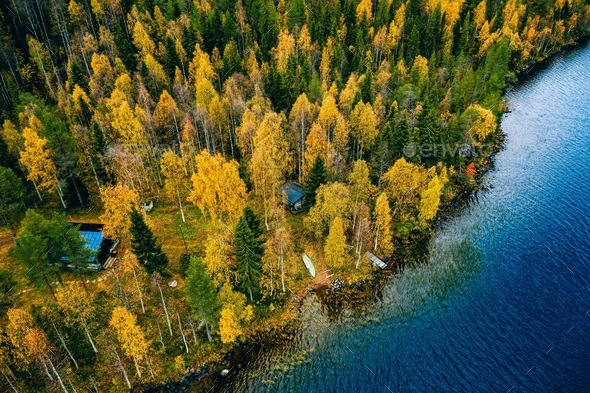 Aerial view of cottage in autumn colors forest by blue lake in rural Finland - Stock Photo - Images