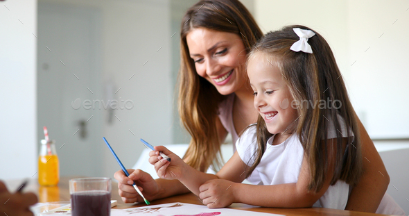 Little girl painting with her mother at home - Stock Photo - Images
