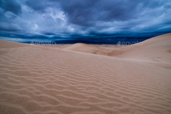 Storm clouds over sand dunes in the desert - Stock Photo - Images