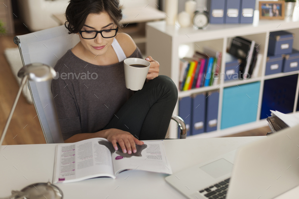 Attractive woman reading magazine at home - Stock Photo - Images