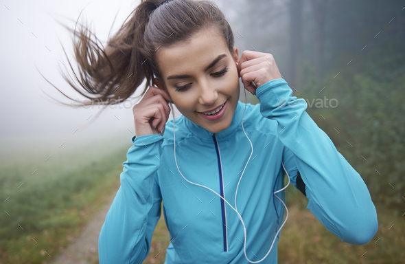 Running is time with her favourite sounds - Stock Photo - Images