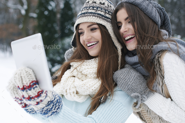 Sharing their online photo album in winter day - Stock Photo - Images