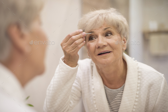 Well-groomed woman in front of the mirror - Stock Photo - Images