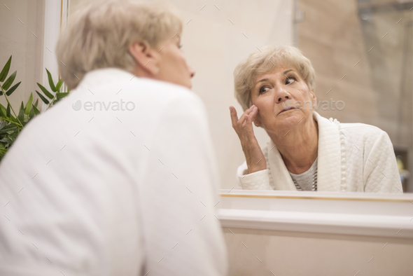Reflection of edery woman in the mirror - Stock Photo - Images