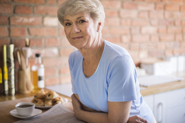 Mature woman standing in the kitchen - Stock Photo - Images