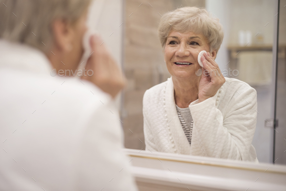 Senior woman standing in front of the mirror - Stock Photo - Images