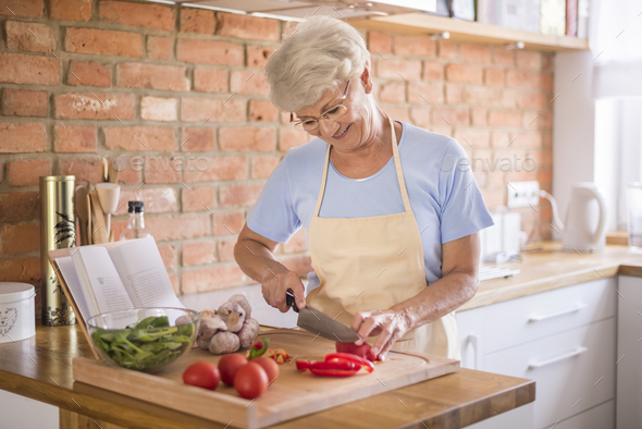 Senior woman cutting vegetables - Stock Photo - Images