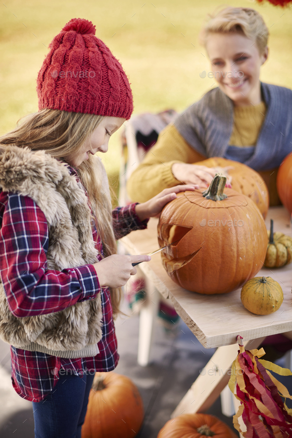 Affectionate girl carving a pumpkin in the garden - Stock Photo - Images