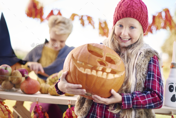Girl is very proud of her homemade jack o'lantern - Stock Photo - Images