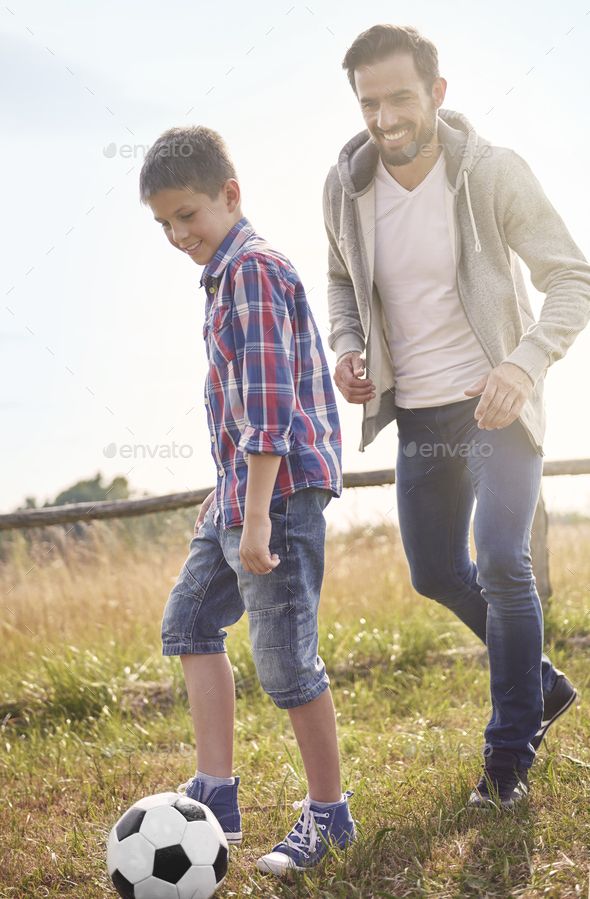Father playing football with his son - Stock Photo - Images