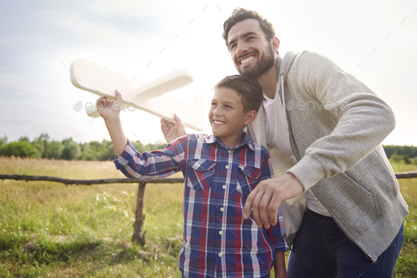 Father and son testing a paper plane - Stock Photo - Images