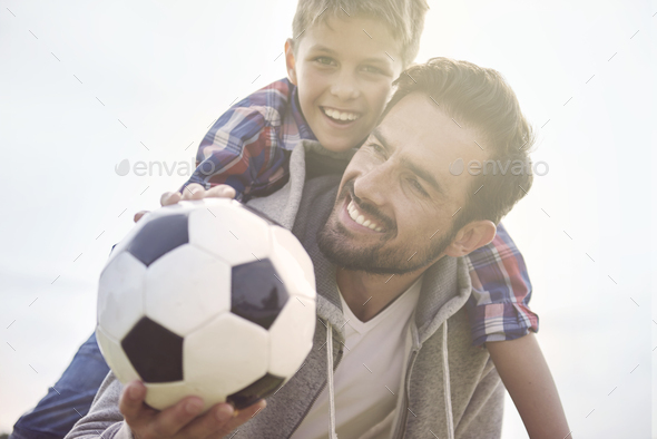 Father teaches teaches son how to play football - Stock Photo - Images