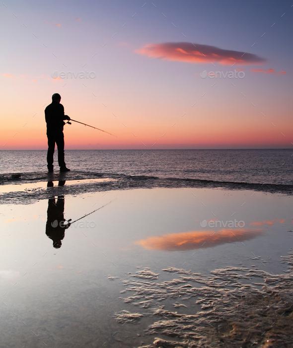 Fishermen at sunrise on the sea pier - Stock Photo - Images