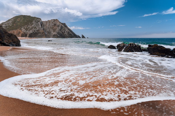 Praia da Adraga at atlantic ocean, Portugal. Foamy wave at sandy beach with picturesque landscape - Stock Photo - Images
