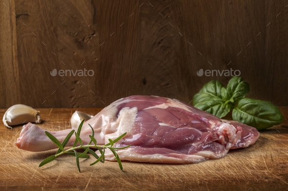 One duck raw leg and herbs on wood - Stock Photo - Images