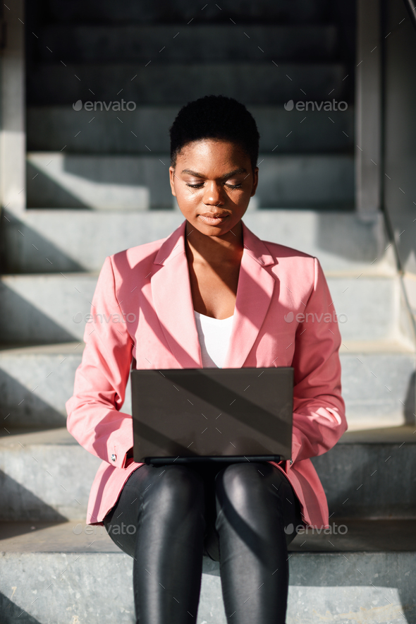 Black woman sitting on urban steps working with a laptop computer - Stock Photo - Images