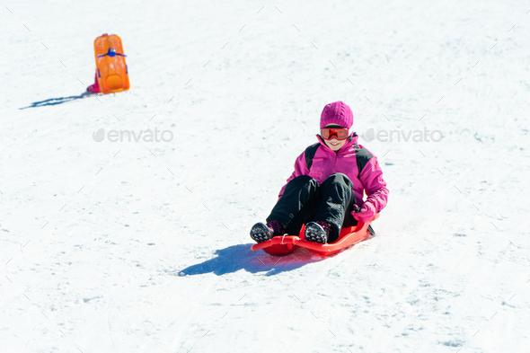 Little girl sledding at Sierra Nevada ski resort - Stock Photo - Images
