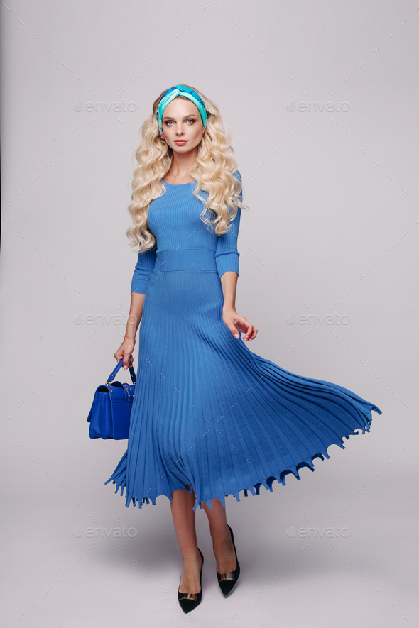 Glamour elegance young blonde woman in blue dress holding small bag at white studio background - Stock Photo - Images