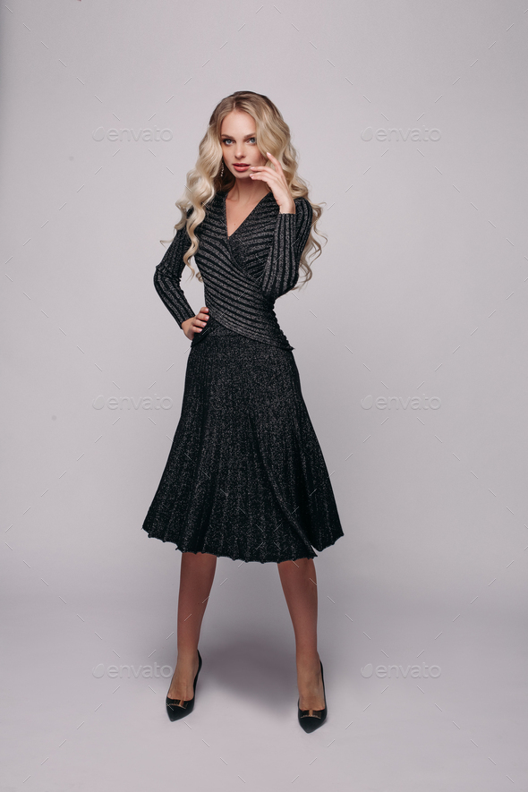 Gorgeous blonde model in ivory dress on grey - Stock Photo - Images